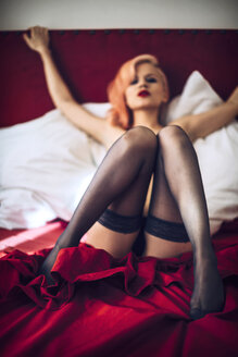 Young woman wearing stockings lying in bed - EHF000313