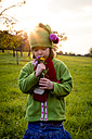 Germany, Baden-Wuerttemberg, little girl on a meadow smelling flowers at evening twilight - LVF004124