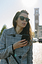 Italy, Vicenza, woman wearing checkered coat and sunglasses holding cell phone - GIOF000462