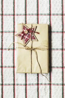 Wrapped Christmas present on checked cloth - AKNF000029