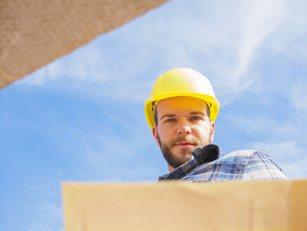 Portrait of foreman with construction plan in front of sky - LAF001547