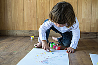 Little boy crouching on wooden floor painting with finger colours - KIJF000002