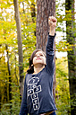 Portrait of girl playing superwoman in the woods - LVF004146