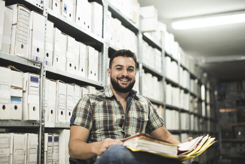Portrait of smiling bearded man with a folder in an archive - JASF000235