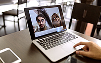 Funny photography of young couple on display of laptop - MGOF001008