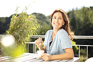 Relaxed woman on balcony with cup of coffee - TOYF001433