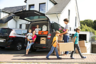 Happy family at driveway carrying cardboard boxes - TOYF001439