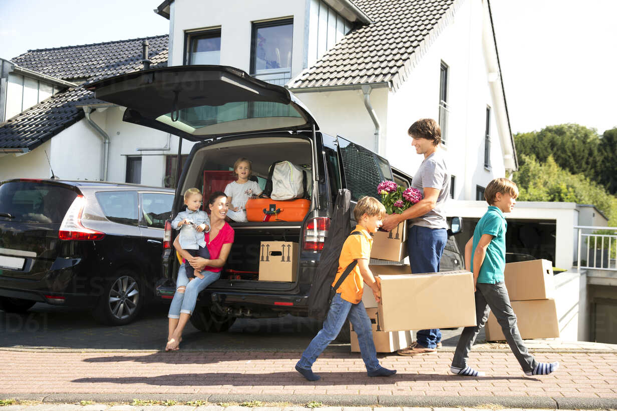 Happy family at driveway carrying cardboard boxes - TOYF001439 - Tomas Rodriguez/Westend61