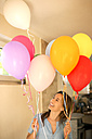 Happy woman standing holding colorful balloons - TOYF001445