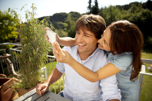 Happy couple on balcony taking a selfie - TOYF001457