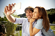 Happy couple on balcony taking a selfie - TOYF001460