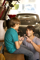 Father and son in garage with vintage car and tools - TOYF001463