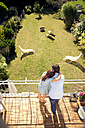 Couple embracing on balcony above garden - TOYF001466
