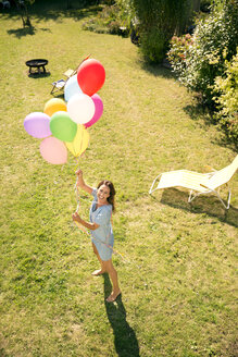 Happy woman standing in garden holding colorful balloons - TOYF001469