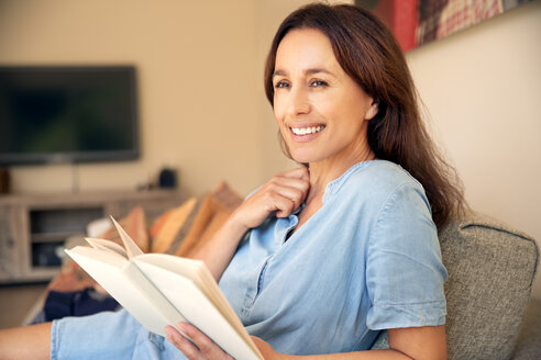 Smiling woman reading a book on couch - TOYF001472