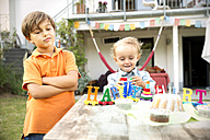Happy toddler celebrating birthday in garden with displeases brother standing besides - TOYF001484