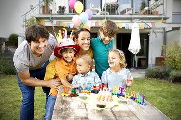 Happy family having a children's birthday party in garden - TOYF001487