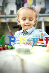 Happy toddler celebrating birthday in garden - TOYF001490