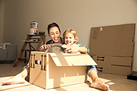Happy woman with daughter sitting in cardboard box - TOYF001493