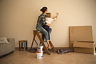 Mother and daughter painting a wall - TOYF001496