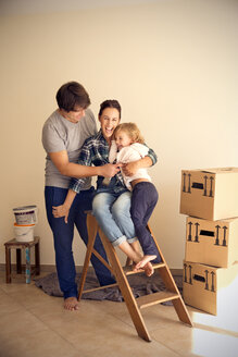 Happy family on step ladder beside cardboard boxes - TOYF001499