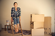 Smiling woman sitting on step ladder beside cardboard boxes - TOYF001502