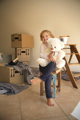 Girl with teddy bear and cardboard boxes in background - TOYF001511