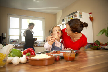 Happy mother and daughter in kitchen preparing pizza with father in background - TOYF001514