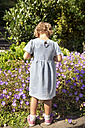 Girl in summer dress standing at flowers - TOYF001523