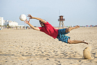 Spain, Cadiz, El Puerto de Santa Maria, Man playing soccer on the beach - KIJF000009