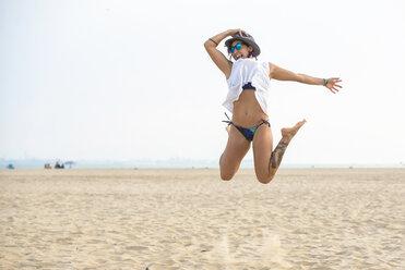 Spain, Cadiz, El Puerto de Santa Maria, Woman jumping on the beach - KIJF000015