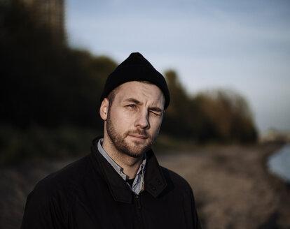 Portrait of winking man wearing woolly hat - DASF000026