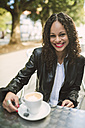 Portrait of smiling young woman with cup of coffee - RAEF000621