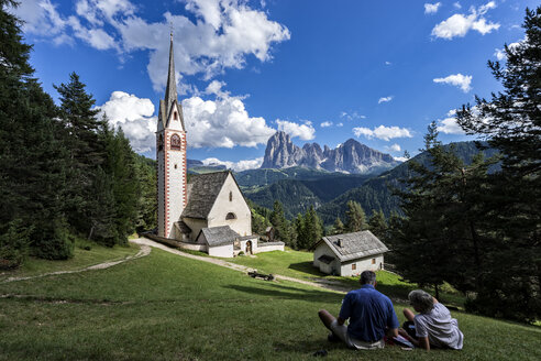 Italy, Dolomites, Church of Saint Jacob, near Ortisei, with two hikers resting, Langkofel and Plattkofel in the background - LOM000082