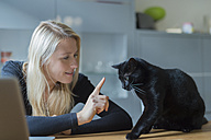 Woman reproving her cat sitting on dining table - FRF000353