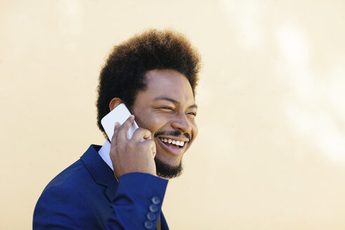 Portrait of smiling young businessman telephoning with smartphone - EBSF001010