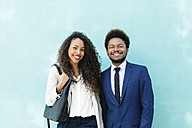 Portrait of two smiling young business people in front of blue wall - EBSF001013