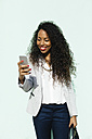 Portrait of smiling young businesswoman looking at her smartphone - EBSF001016