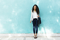 Portrait of smiling young businesswoman with leather bag standing in front of a blue wall - EBSF001019
