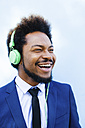 Portrait of smiling young businessman hearing music with headphones - EBSF001022