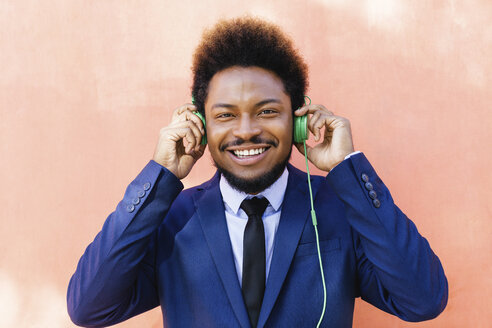 Portrait of smiling young businessman hearing music with headphones - EBSF001025