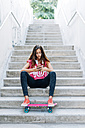 Portrait of young girl sitting on stairs with her skateboard using smartphone - GEMF000468