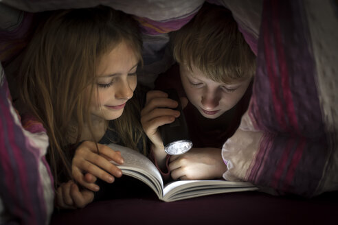 Brother and sister reading book under a blanket - SARF002302