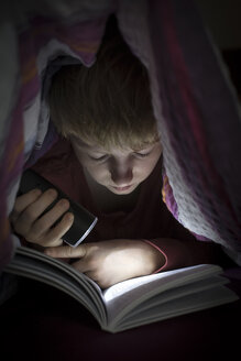 Boy with torch reading book under a blanket - SARF002305