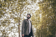 Spain, Tarragona, portrait of bearded young man standing in front of autumnal trees - JRFF000175