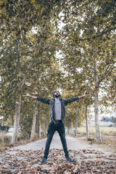 Spain, Tarragona, young man standing on country road throwing autumn leaves in the air - JRFF000181
