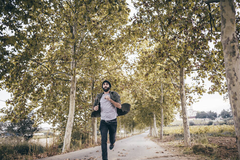 Spain, Tarragona, young man running on autumnal country road - JRFF000184