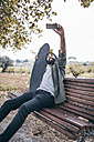 Spain, Tarragona, young man sitting on a bench with his longboard taking a selfie with smartphone - JRFF000187
