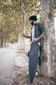 Spain, Tarragona, young man with longboard leaning against tree trunk looking at his smartphone - JRFF000190