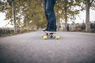 Man standing on longboard on a country road, partial view - JRFF000196